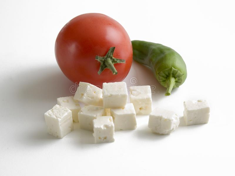 Still life formed by a red tomato, a green pepper and cubes of fresh cheese royalty free stock photos