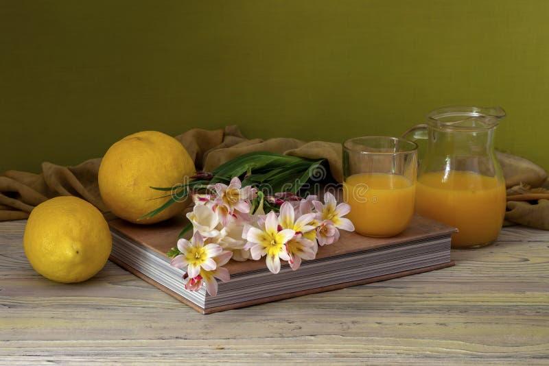 Still life with freesia, lemons and orange juice stock photography