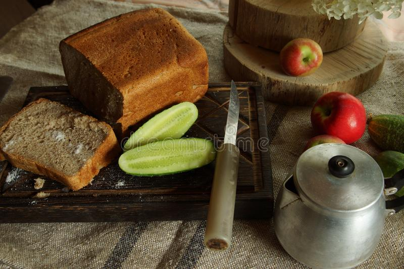 Still life with fresh bread and salt, next to a green cucumber from the garden, rustic style royalty free stock photography
