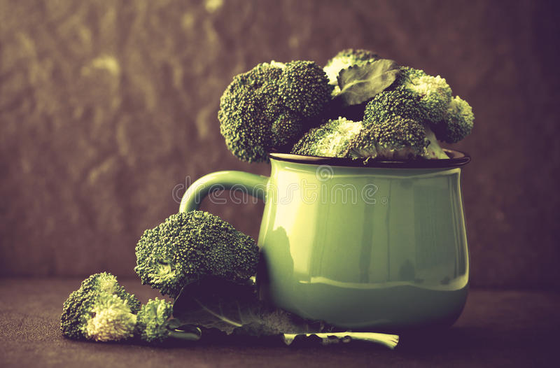 still life with fresh green broccoli in ceramic cup on black stone plate , vintage and retro color tone royalty free stock image