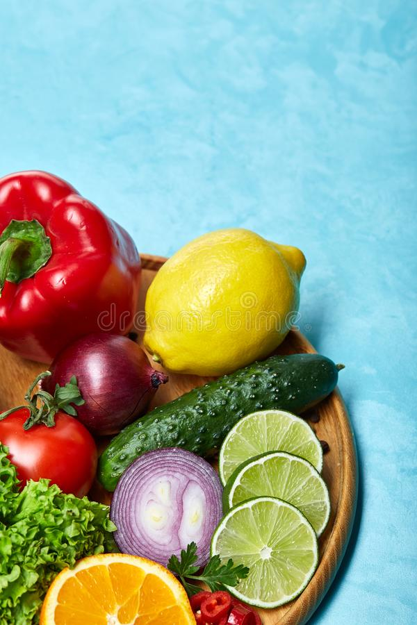 Still life of fresh organic vegetables on wooden plate over blue background, selective focus, close-up stock photo