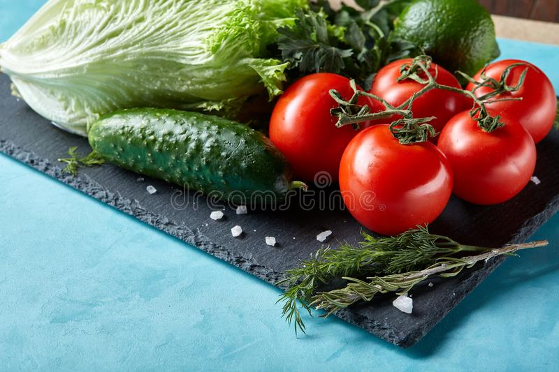 Still life of fresh organic vegetables on wooden plate over blue background, selective focus, close-up royalty free stock photos
