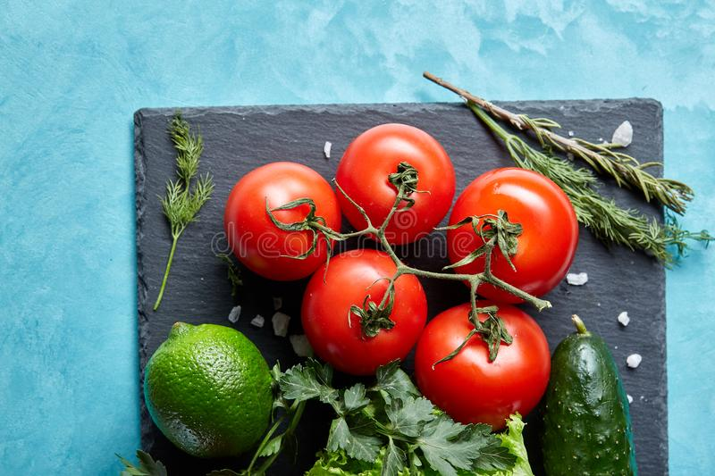Still life of fresh organic vegetables on wooden plate over blue background, selective focus, close-up stock images