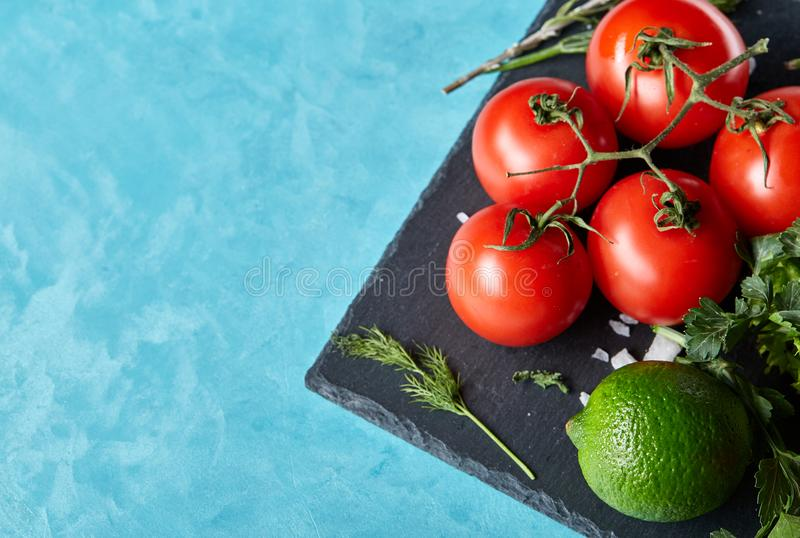Still life of fresh organic vegetables on wooden plate over blue background, selective focus, close-up stock image