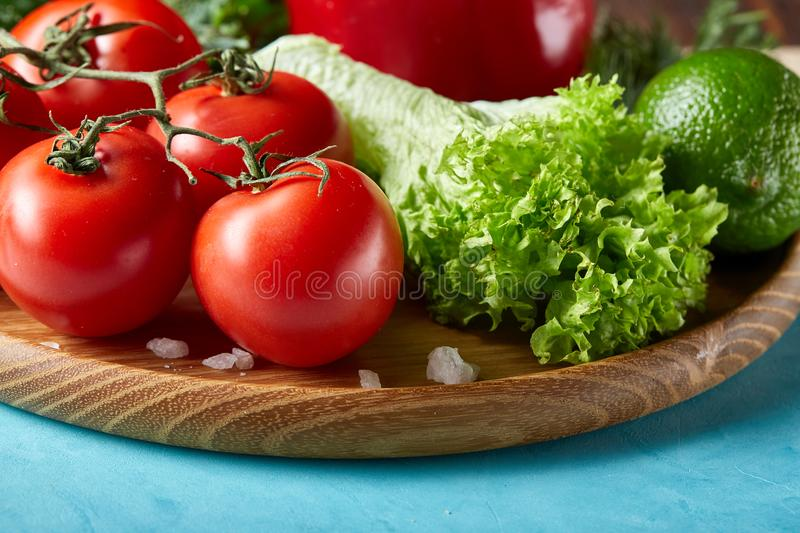 Still life of fresh organic vegetables on wooden plate over blue background, selective focus, close-up stock photos