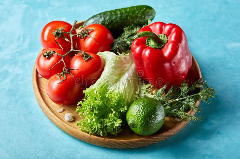 Still life of fresh organic vegetables on wooden plate over blue background, selective focus, close-up royalty free stock images