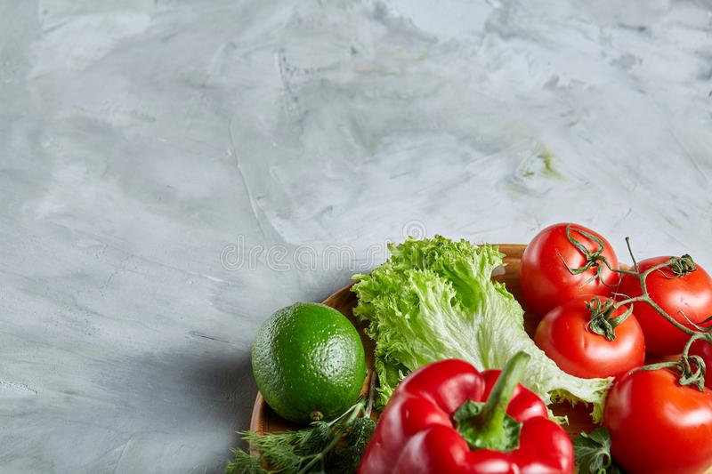 Still life of fresh organic vegetables on wooden plate over white background, selective focus, close-up stock photo