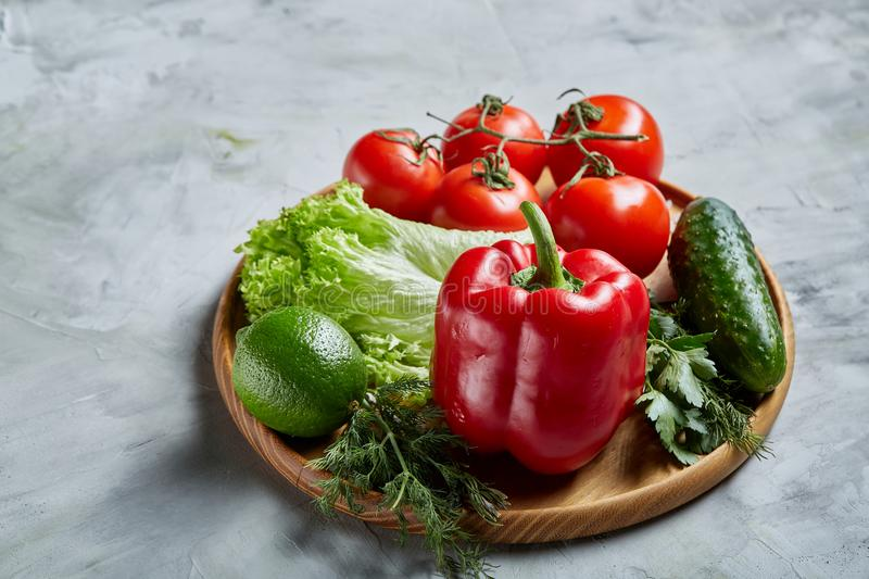 Still life of fresh organic vegetables on wooden plate over white background, selective focus, close-up stock image
