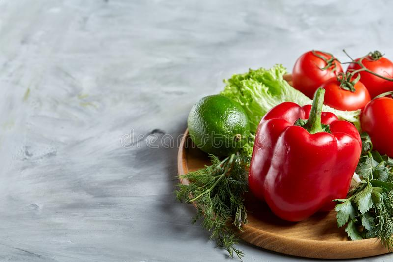 Still life of fresh organic vegetables on wooden plate over white background, selective focus, close-up stock images