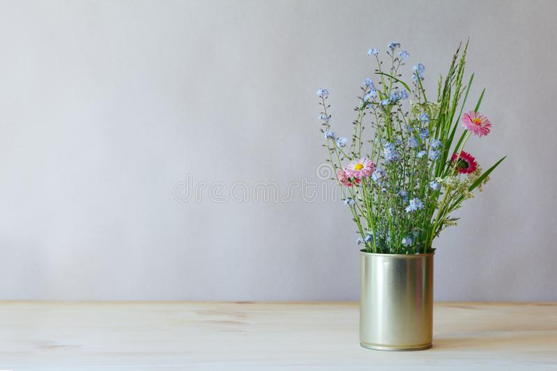 Still life fresh tender fragile beautiful wildflowers and green grass in metal can on wooden table on gray background stock photos