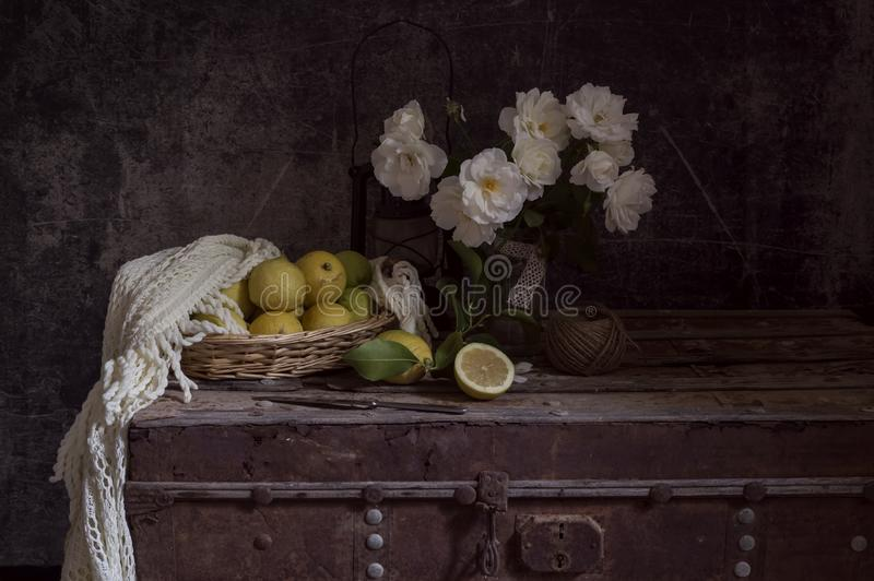 Still life with roses on a old box and lemons close-up stock photography