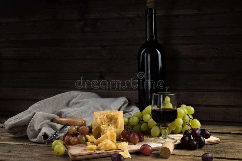 Still life from fruit, cheese and wine. The piece of hard cheese lies on a chopping board. Clusters of red and green mature grapes stock images