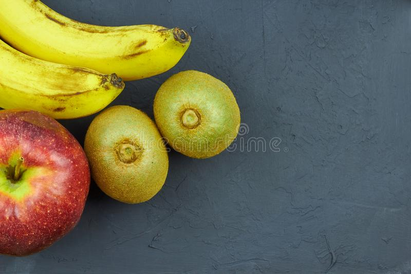 Still life with fruit. Close up view of red apples, bananas and kiwi on dark background with copy space royalty free stock photos