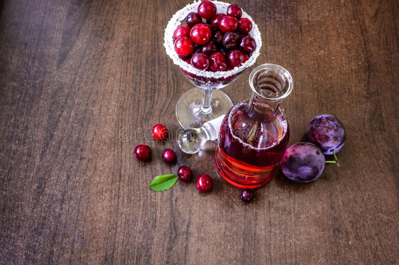 still life of fruit and wine. Cherry wine in the carafe, in a glass of cherries, on a wooden table cherry and plum stock images