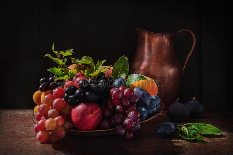 Still life with fruits: grape, apple, fig, pear and peach on the antique copper tin plate and a cooper jug near royalty free stock images