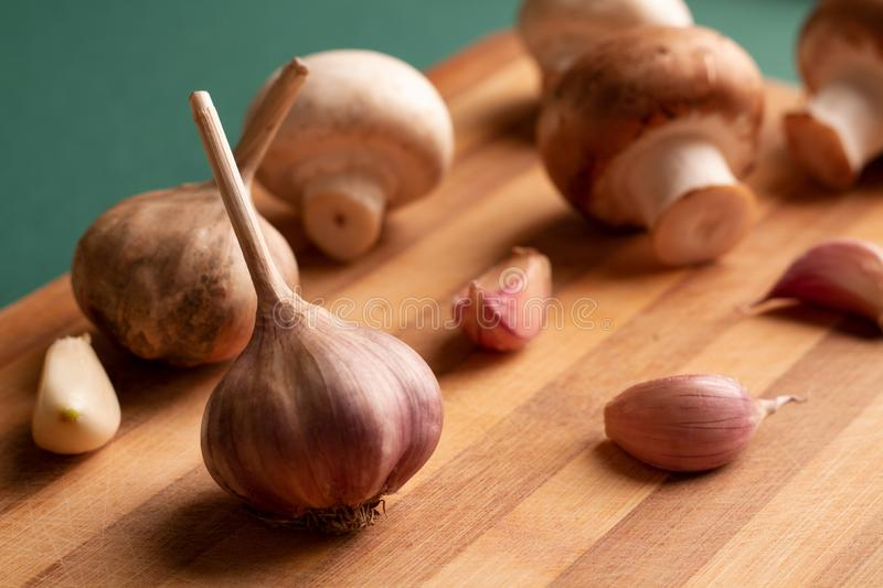 Still life of garlic and mushrooms laid out on a wooden board royalty free stock images