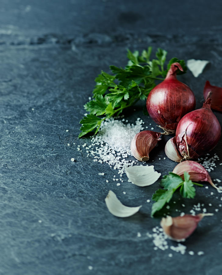 Still life with garlic, onion, parsley and sea salt royalty free stock images