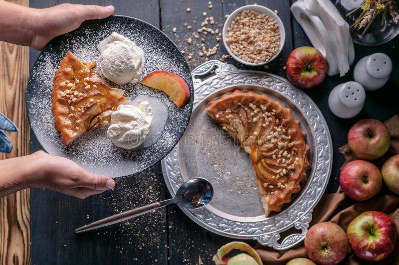Still life: a girl holds a homemade pie with apples, peaches and ice cream. Close-up stock image