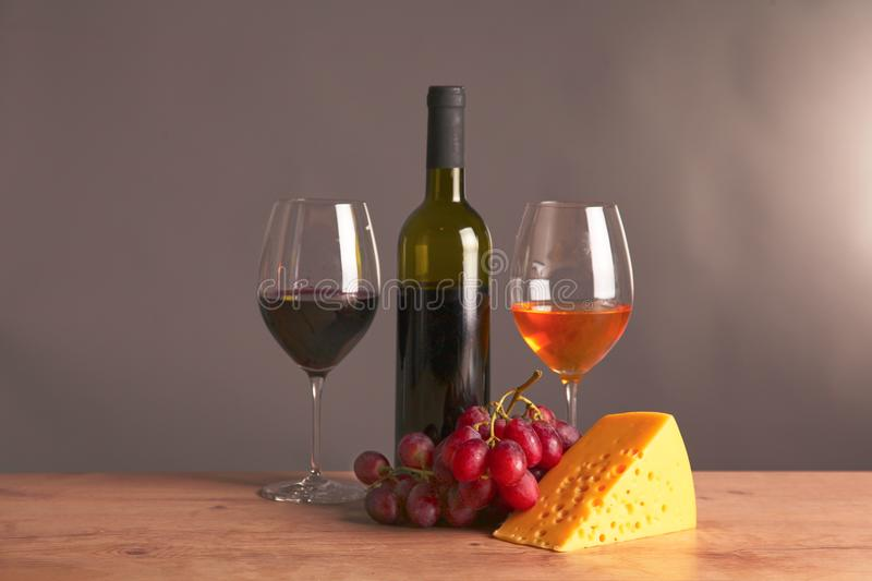 Still life with glass and bottle of wine, cheese and grapes royalty free stock photo