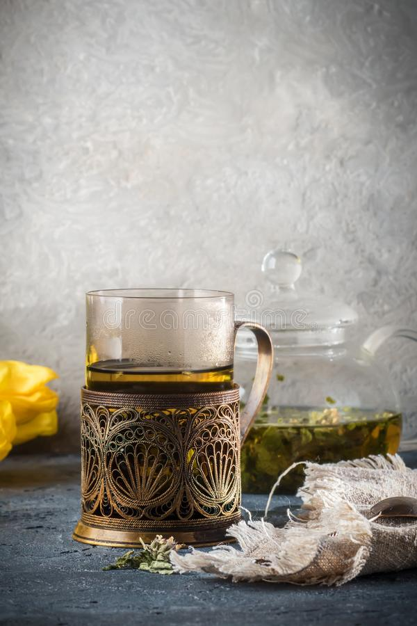 Still life with glass cup mug of tea in vintage retro stand and royalty free stock photography