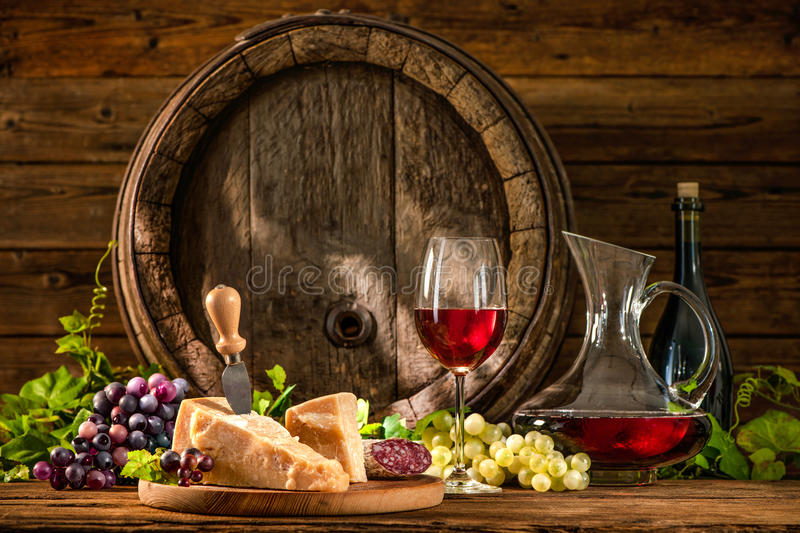 Still life with glass of red wine. And old oak wine barrel stock images