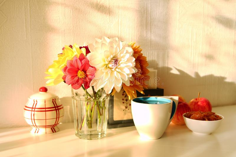 Still life with glass vase with colorful flowers of peonies, cup of tea, apple jam, apples and sugar bowl on the white table. stock photo