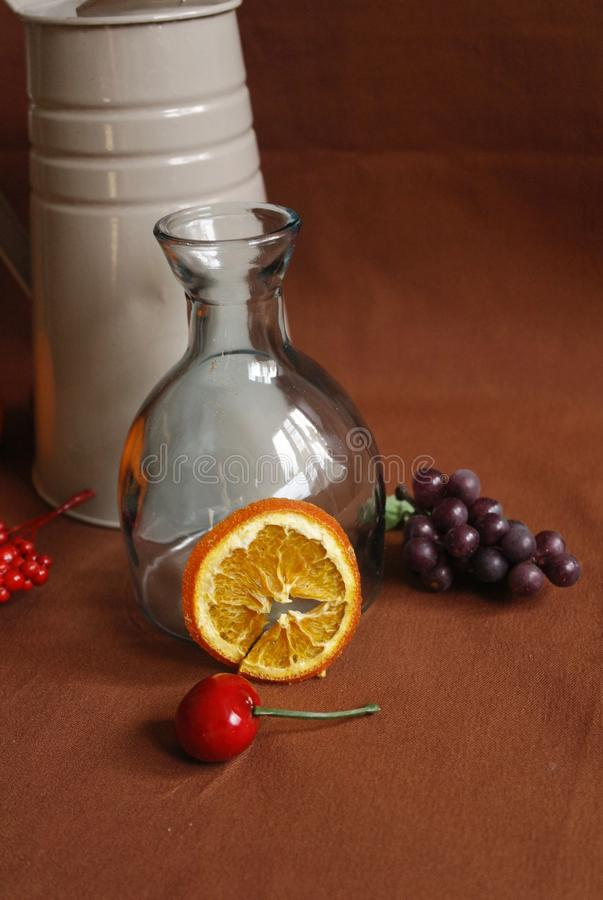 Still life with a glass vase with a watering can and an orange slice. Still life with a glass vase with a gray watering can, fruit and an orange slice royalty free stock image
