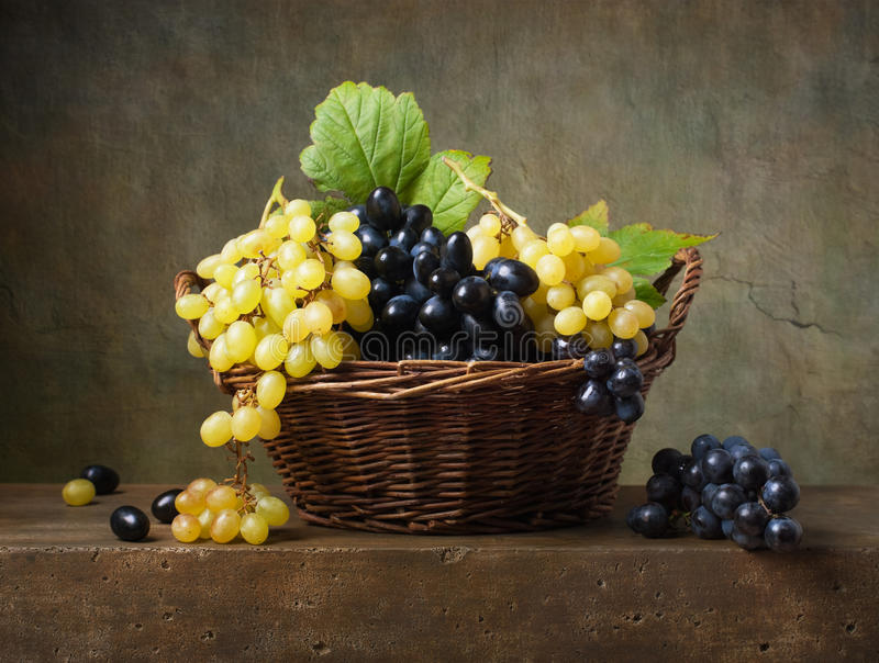Still life with grapes. In a basket on the table royalty free stock photo
