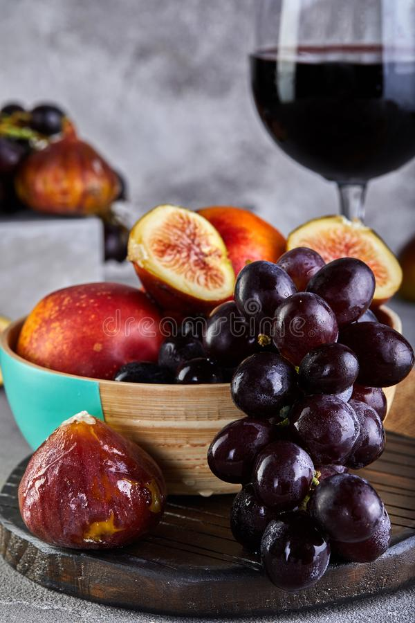 Still life of grapes, peaches, figs and glasses of red wine on a gray stock photo