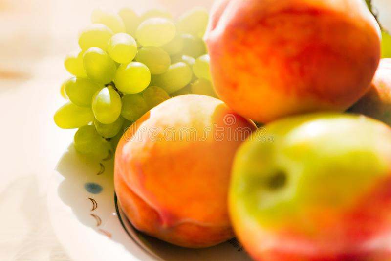 Still life of grapes of two peaches and an apple close-up in soft focus stock photo