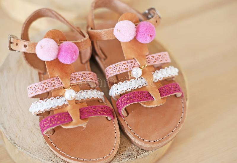 Greek leather sandals with pink tassel and pom pom for girls - kids shoes advertisement royalty free stock image