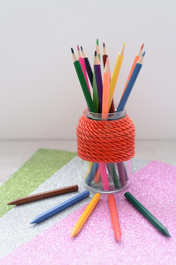 Still life a green mug filled with colorful pencils against a red brick wall stock photos