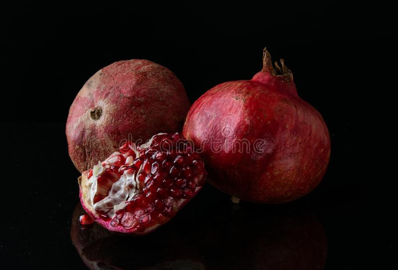 Still life grenade fruit. Feed on a black background. stock image