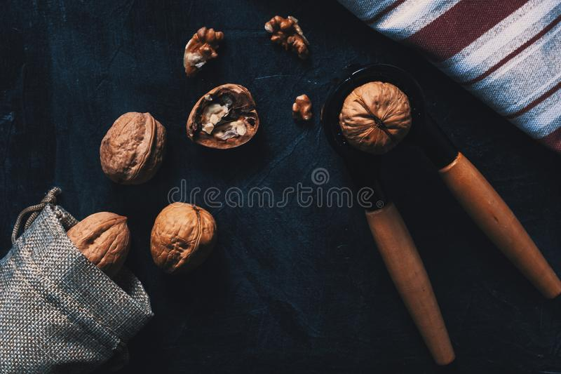 Still life of a group of nuts and a nutcracker. Overhead picture of still life of a group of nuts coming out of a rustic bag and a nutcracker, on dark board and royalty free stock image