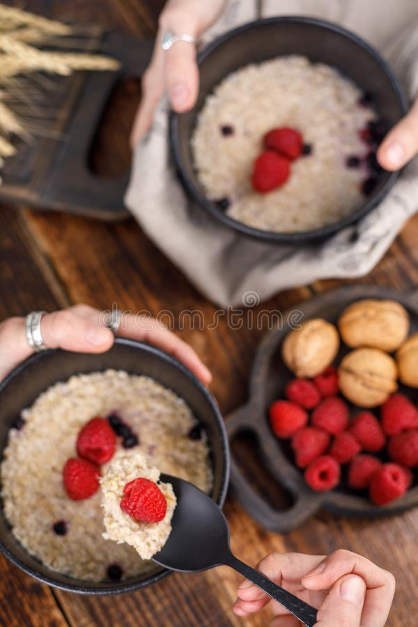 Still life with hands that hold exquisite ceramic bowls with oatmeal and fresh raspberries on a wooden backgroun. stock photography