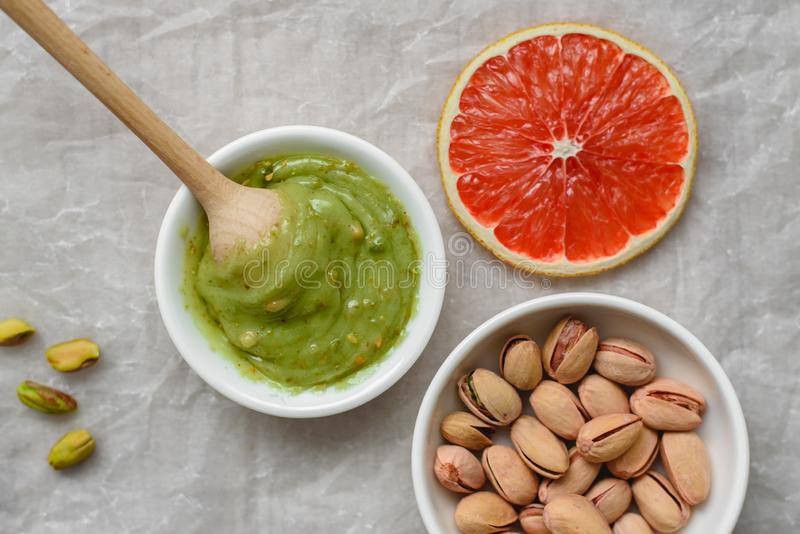 Still life of healthy food, pistachio paste, peeled and unpeeled salted pistachios, grapefruit, wooden spoon on a light background royalty free stock photography