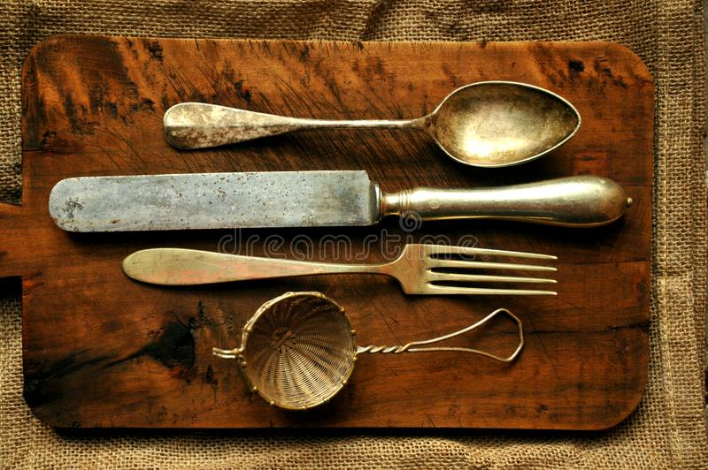 Still life image with old spoon, knife , fork and strainer. Vintage cutlery on a wooden background . kithcen, cuisine art concept stock photo