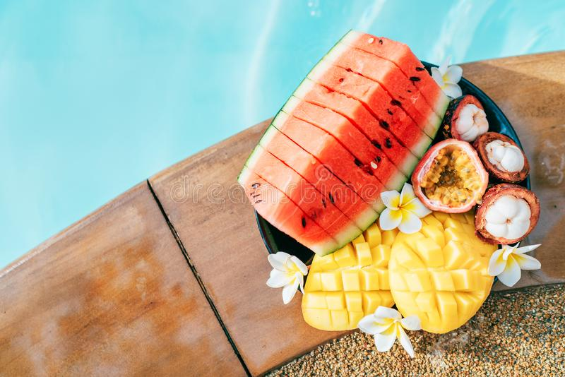 Still life image of tropical fruits and flowers near the pool: water melon, mango, mangosteen, passion fruit stock photos