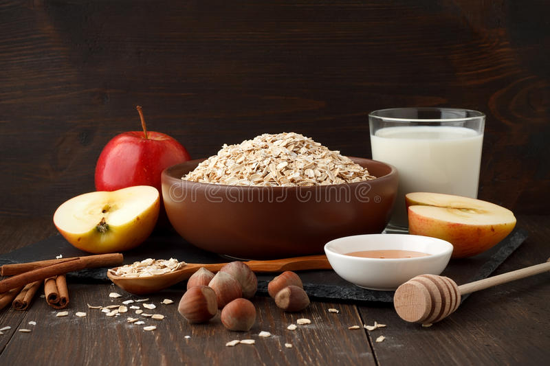 Still life of ingredients for healthy breakfast: rolled oat flakes, milk, apple, honey, hazelnut, cinnamon. stock image