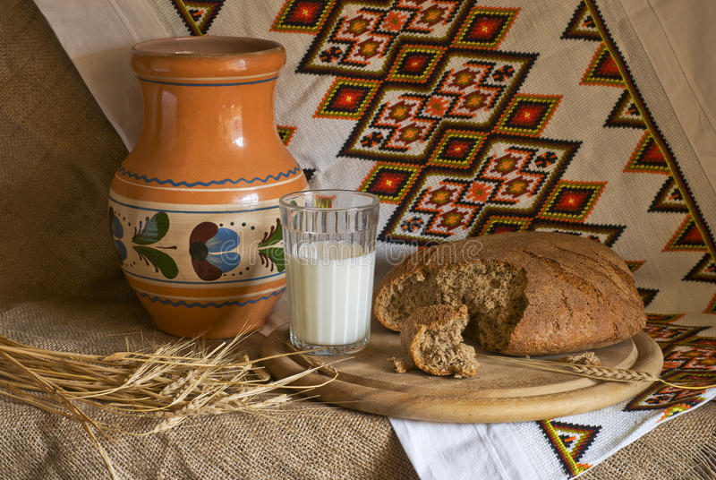 Still life with a jug bread glass of milk ears. Decorative pattern stock image