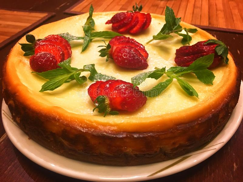 Cheesecake cake decorated with mint leaves and strawberries stock photography