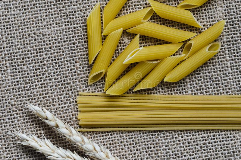 Still life for a kitchen of wheat ears and pasta from wheat on a sackcloth background Made in Kazakhstan stock image