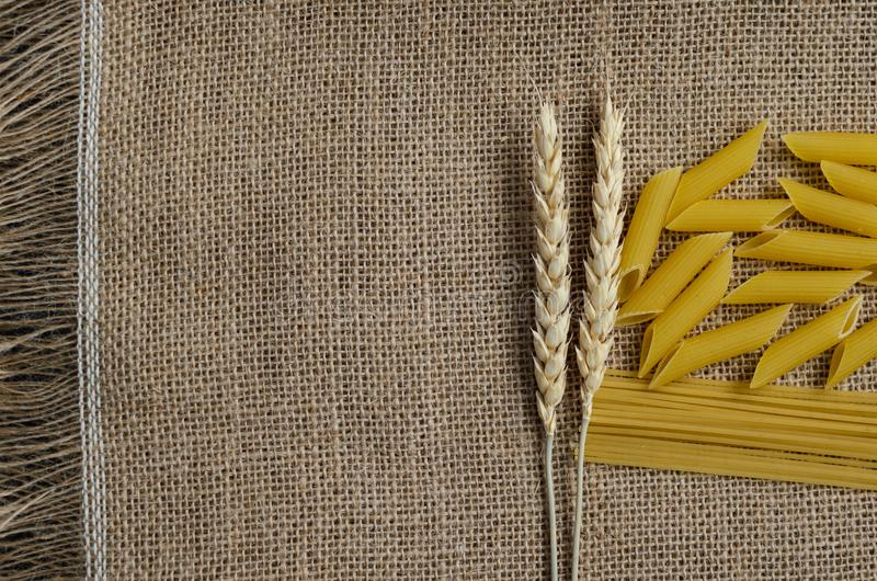 Still life for a kitchen of wheat ears and pasta from wheat on a sackcloth background Made in Kazakhstan royalty free stock images