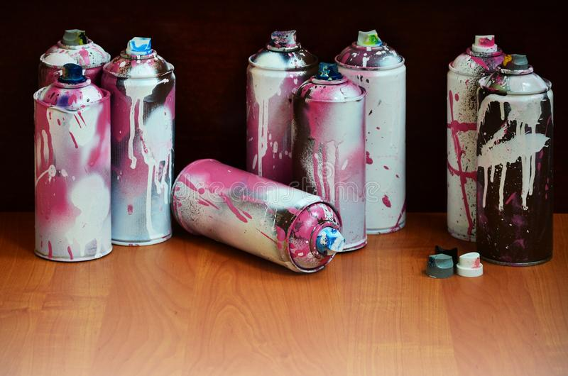 Still life with a large number of used colorful spray cans of aerosol paint lying on the treated wooden surface in the artist`s g. Raffiti workshop. Dirty and royalty free stock photo