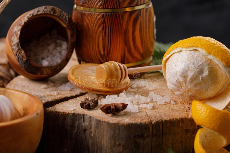 Still life with lemon and honey, on a wooden background in a rustic style. The concept of treating colds. Ethnoscience. Close-up royalty free stock photography