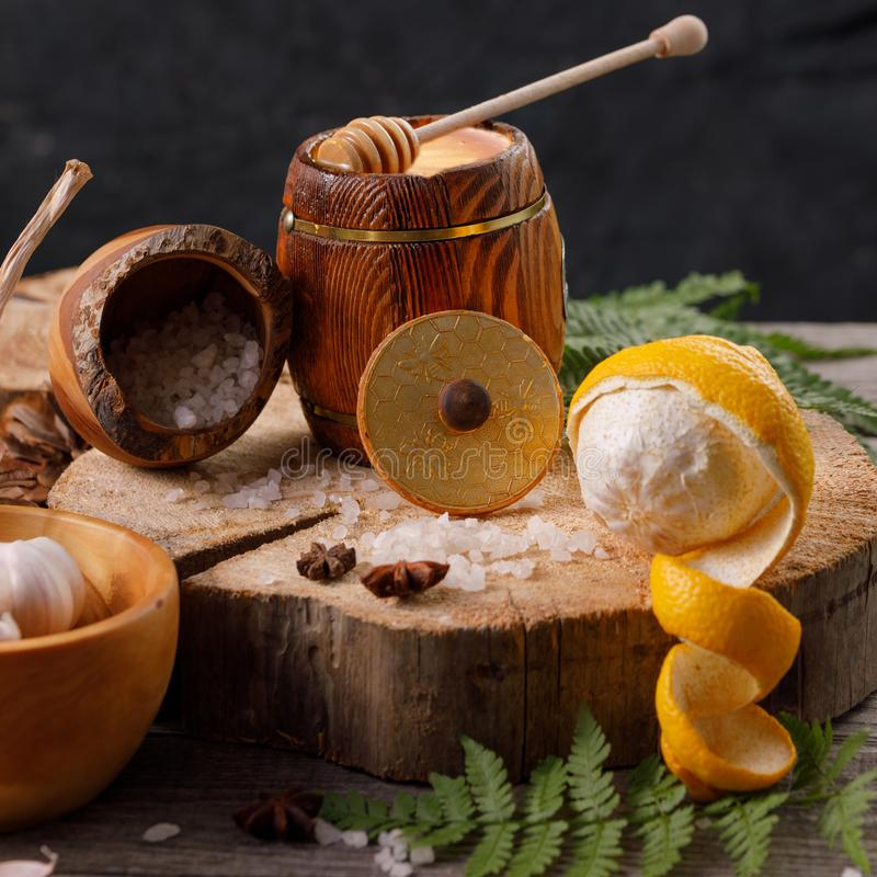 Still life with lemon and honey, on a wooden background in a rustic style. The concept of treating colds. Ethnoscience. Close-up royalty free stock images