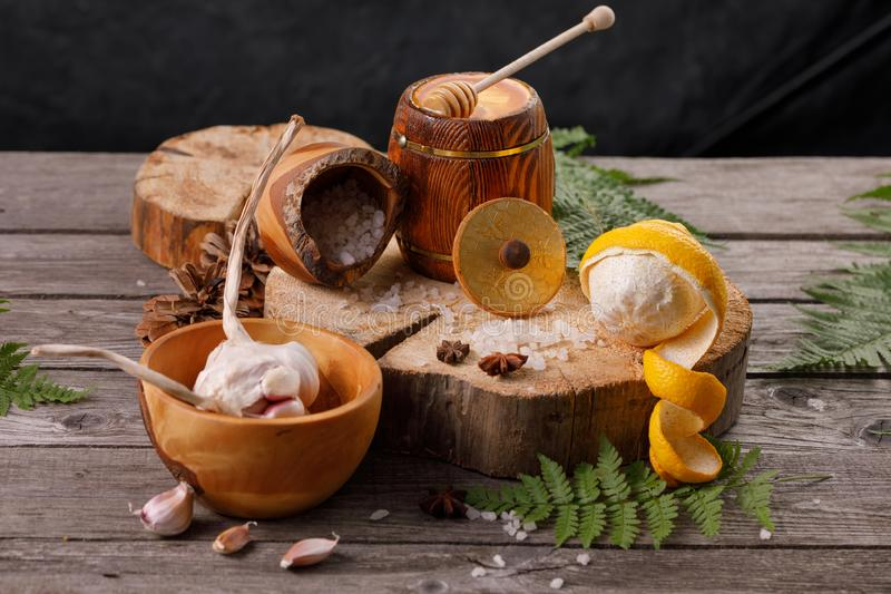 Still life with lemon and honey, on a wooden background in a rustic style. The concept of treating colds. Ethnoscience. Close-up royalty free stock photo