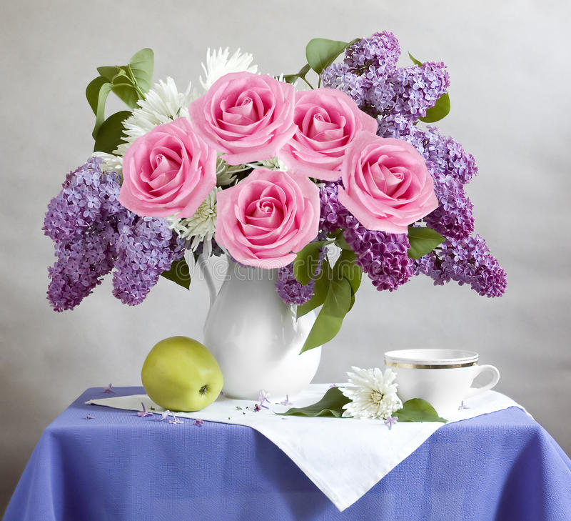 Still life with lilac flowers. Roses, apple and cup stock photo