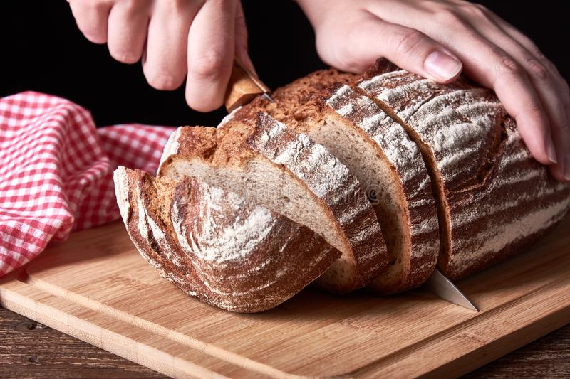 Still life with a loaf of bread sliced. Female hand holding kitchen knife. Old wooden table desk. Still life with a loaf of bread sliced. Female hand holding royalty free stock image