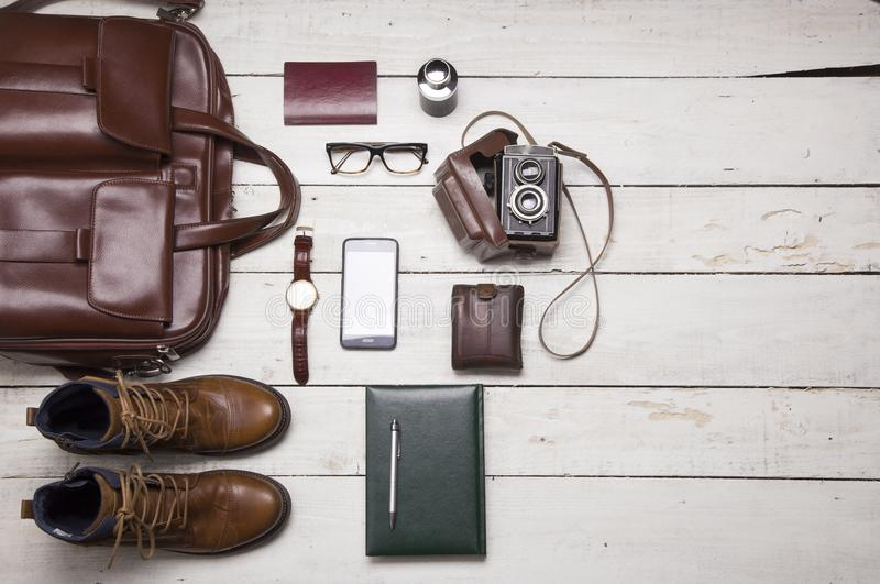 Still life with Men`s casual outfits with leather accessories on. Brown wooden background, beauty and fashion, travel concept royalty free stock image